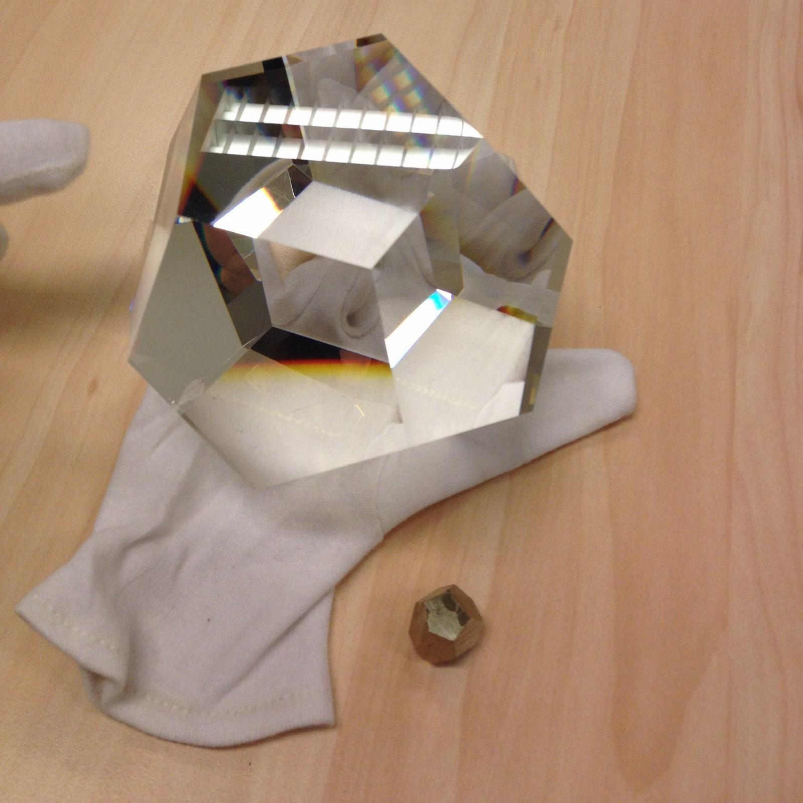 Een Dodecaëder van optisch glas met daaronder een Pyritoëder uit Spanje, Ambas Aguas.