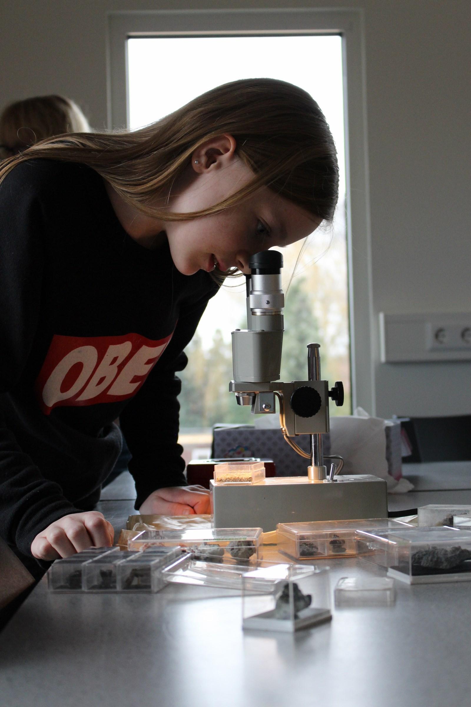 Een Geo Oss jeugdlid die geconcentreerd naar micromounts kijkt door een microscoop.